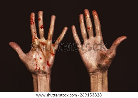 Beautiful man's hands in golden and red paint on black background  - stock photo