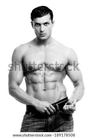 Beautiful man with muscular body holding the belt. - stock photo