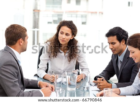 Beautiful manager speaking with her team during a meeting at the office - stock photo