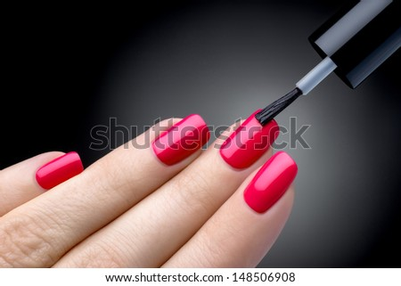 Beautiful manicure process. Nail polish being applied to hand, polish is a red color. Black background closeup. - stock photo