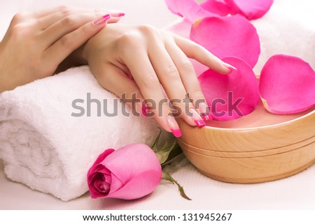 beautiful manicure with fragrant rose petals and towel