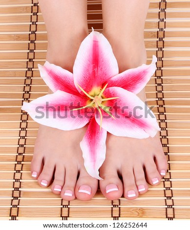 beautiful manicured female bare feet with pink lily flower over bamboo mat feet care,  spa - stock photo