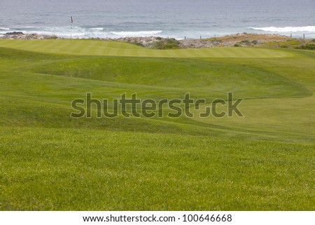 Beautiful, manicured golf course greens on a softly rolling hilly topography leading to the hole. The putting green is located right by the ocean, with small waves washing into shore.
