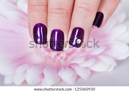 Beautiful manicured nails with purple nail varnish and a tiny crystal displayed alongside a pink dahlia
