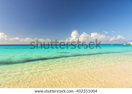 Beautiful marine view on sea coast line with clean wavy surf water on sandy beach with boats and yachts on horizon and cloudy blue sky at sunny day - stock photo