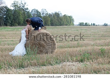 Beautiful married couple acting very romantic on a field of bales. He climbs the bale to kiss her lips while she lays her head to be kissed.  - stock photo