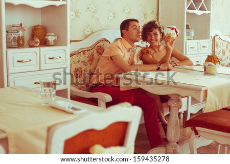 Beautiful married couple of hipsters in trendy clothing sitting in vintage cafe with white furniture. Vintage design and accessories. Wedding day. Daylight. Indoor shot