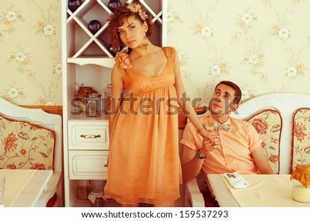 Beautiful married couple of hipsters in trendy clothing sitting in vintage cafe with white furniture. Vintage design and accessories. Wedding day. Daylight. Copy-space. Indoor shot