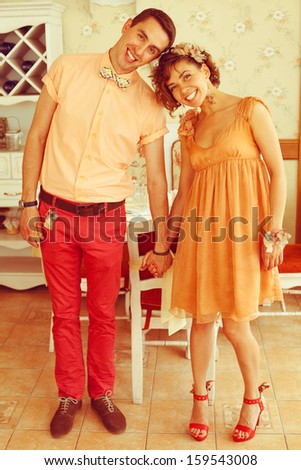 Beautiful married couple of hipsters in trendy clothing standing and smiling  in vintage cafe with white furniture. Vintage design and accessories. Wedding day. Daylight. Indoor shot
