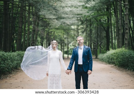 Beautiful married young couple standing with brides veil waving in the wind in the forest all alone - stock photo