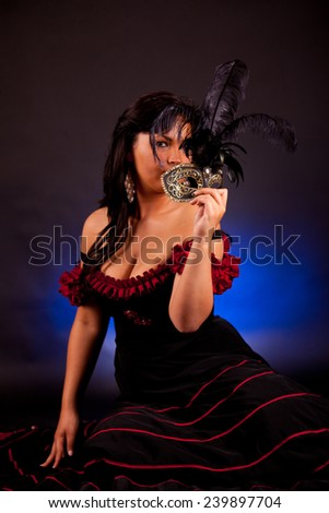 Beautiful masked young woman on black background