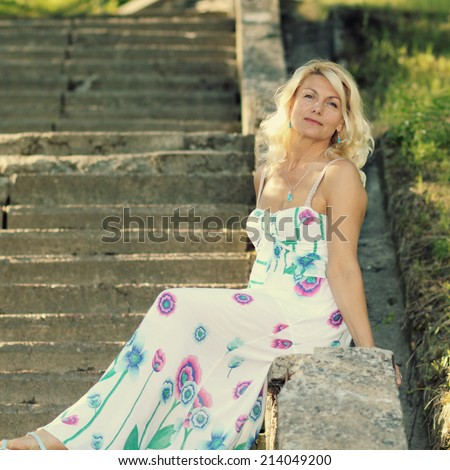 Beautiful mature blonde in a vintage dress posing on a stone staircase.