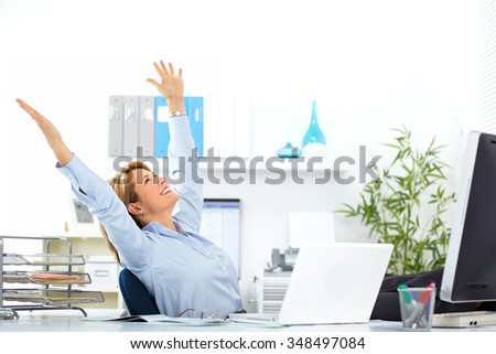Beautiful mature business woman relaxing in modern office. - stock photo