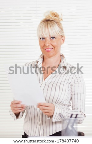 Beautiful mature Business woman standing in the office with document.