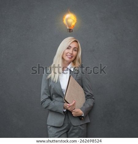 Beautiful mature business woman with idea light bulb above head on gray background