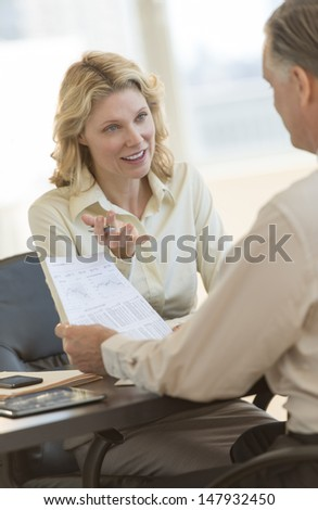 Beautiful mature businesswoman explaining report to male colleague in office