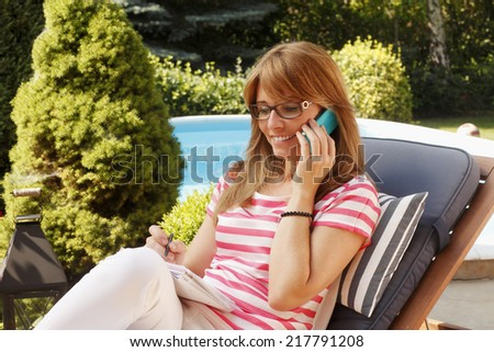 Beautiful mature businesswoman using her mobile, while sitting at garden and working.  - stock photo