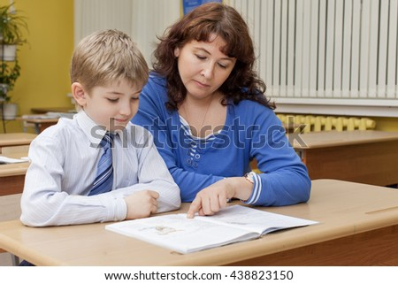 Beautiful mature caucasian teacher with a student reading a textbook at a desk in primary school classroom - stock photo