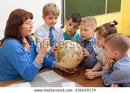 Beautiful, mature caucasian teacher with elementary school students considering a globe around the table. Horizontal color image. - stock photo