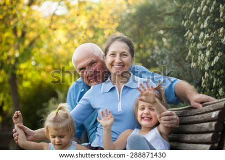 beautiful mature couple with children sitting on bench in autumn park. - stock photo