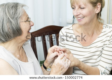 Beautiful mature daughter holding hands her senior mother. - stock photo