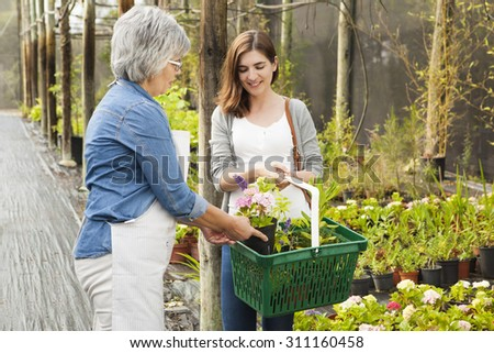 Beautiful mature florist helping a female customer to choose plants