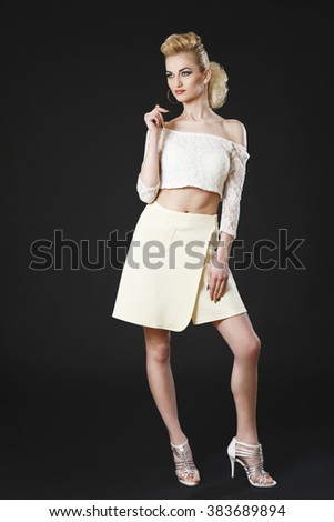 Beautiful mature girl posing in white top and skirt on black background - stock photo