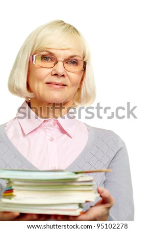 Beautiful mature lady holding a pile of notebooks books and smiling at camera