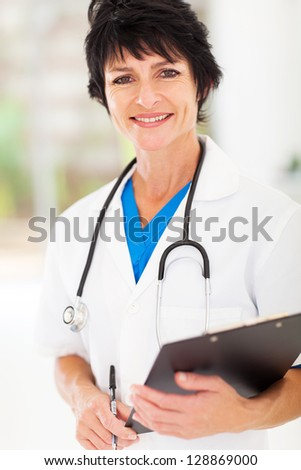 beautiful mature medical nurse portrait in office - stock photo