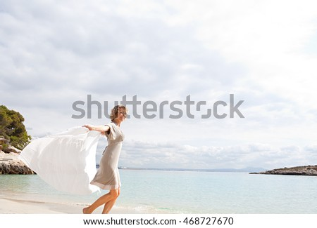 Beautiful mature tourist woman playful running on destination beach with blue sea, holding floating fabric, smiling joyful and looking, sunny outdoors. Healthy travel lifestyle.