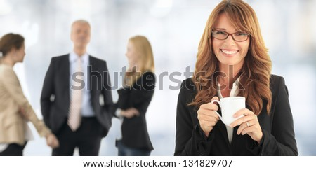 Beautiful mature woman drinking a cup of coffee. With her colleagues In background.