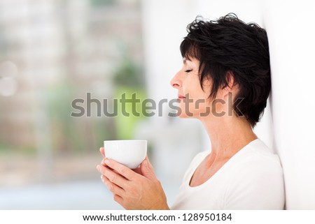 beautiful mature woman enjoying a cup of coffee at home - stock photo