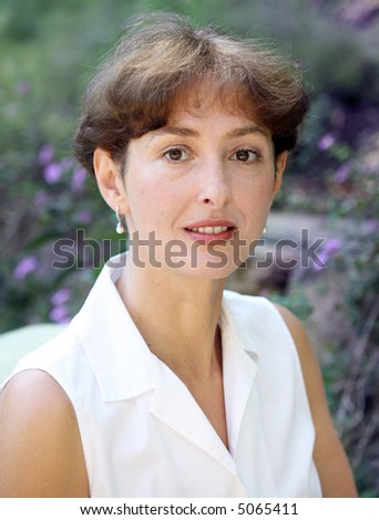 Beautiful mature woman in a white blouse - stock photo