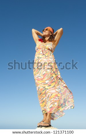 Beautiful mature woman in long summer dress standing relaxed and confident on top of mountain or rock, isolated with blue sky as background and copy space.