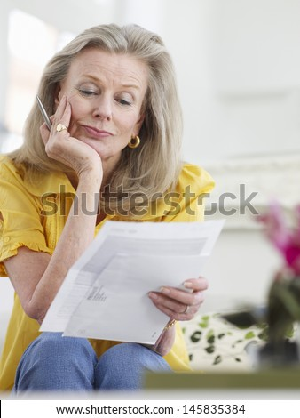 Beautiful mature woman reading documents at home - stock photo