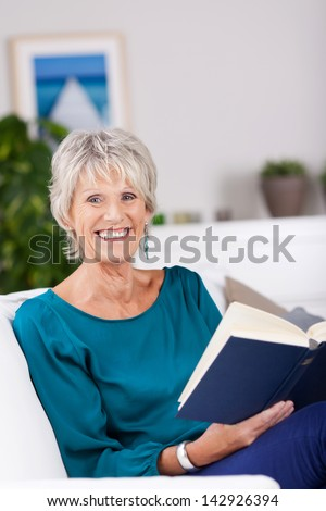 beautiful mature woman reading in a book - stock photo