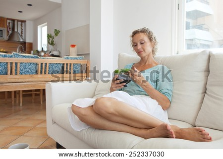 Beautiful mature woman sitting and relaxing on a white sofa at home while eating a small green salad, home interior. Senior woman eating healthy food, wellness and well being indoors. Lifestyle.