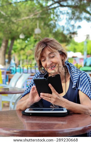 Beautiful  mature woman sitting in the sidewalk cafe holding a smart phone and typing message. - stock photo