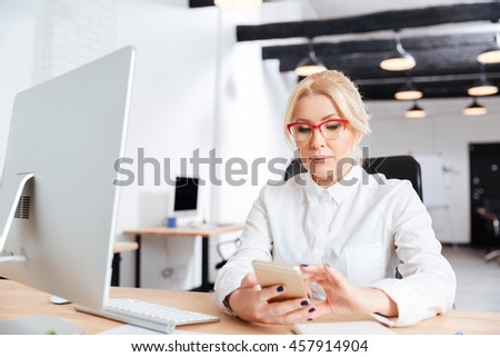 Beautiful mature woman using smart phone in the office - stock photo