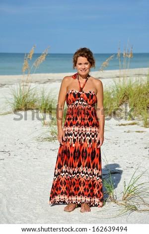 Beautiful Mature Woman Wearing a Sundress on the Beach - stock photo