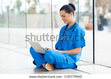 beautiful medical nurse working on laptop - stock photo