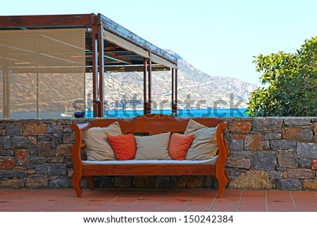 Beautiful mediterranean patio with sea view, stone wall and outdoor sofa with pillows (Greece) - stock photo