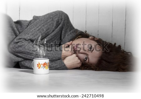 Beautiful melancholic girl lying on the floor with cup of coffee, hot chocolate or tea. Tinted image. - stock photo