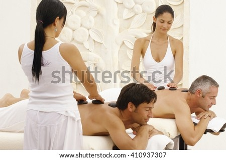Beautiful men relaxed in spa / men having a back massage