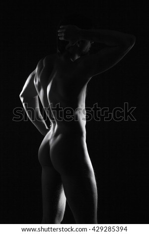 beautiful men's sporty body in backlight on the black background