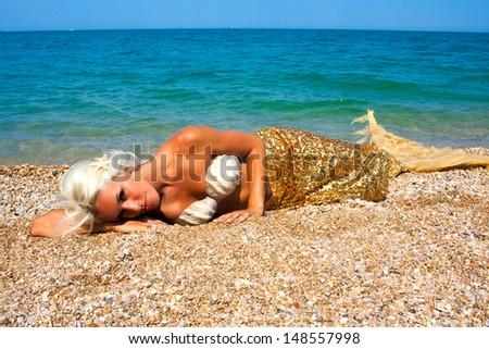 Beautiful mermaid sitting on the rocks near the sea - stock photo