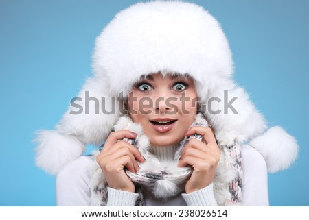 Beautiful merry sexual girl in a white fur cap and warm clothes on a blue background - stock photo