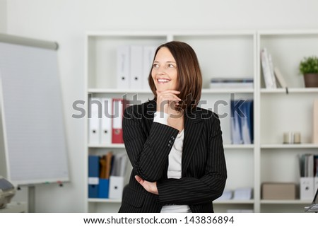 Beautiful mid adult businesswoman with hand on chin looking away while daydreaming in office - stock photo