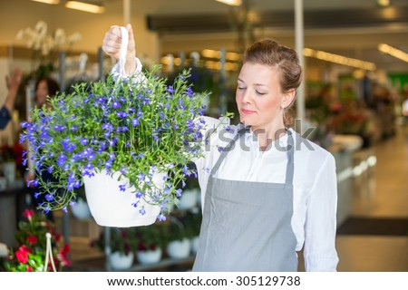 Beautiful mid adult female florist smelling purple flowers in shop - stock photo