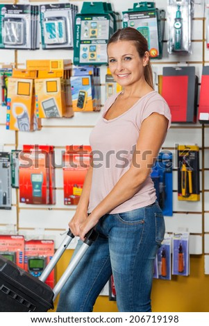 Beautiful mid adult woman looking away while holding tool case in hardware store